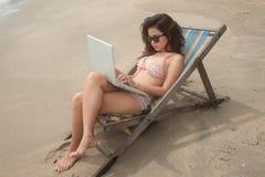 Mujer bastante asiática que trabaja con la computadora portátil en cama de la playa. Imagen de archivo