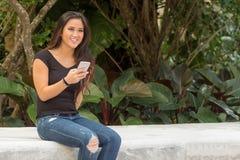 Mujer bastante asiática sonriente de moda de los jóvenes que manda un SMS en el pH elegante Fotografía de archivo libre de regalías
