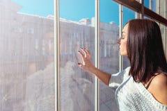 Mujer bastante atractiva que mira la ventana sucia brillante Imagenes de archivo