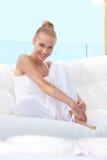 Mujer bastante casual descalzo en el sofá Fotografía de archivo libre de regalías