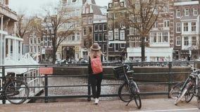 Mujer bastante caucásica que cruza una calle del puente 4K Viajero femenino de moda joven con la mochila que habla en el teléfono almacen de metraje de vídeo
