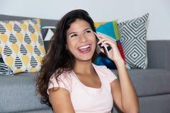Mujer bastante caucásica que se ríe del teléfono móvil Imagen de archivo