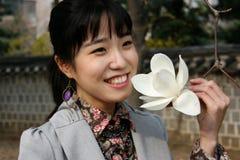 Mujer bastante coreana que sostiene una flor en resorte imágenes de archivo libres de regalías