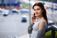 Mujer bastante elegante de los jóvenes que habla en el teléfono elegante en la calle Imagen de archivo