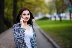 Mujer bastante elegante de los jóvenes que habla en el teléfono elegante en el PA de la ciudad Imagenes de archivo