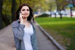 Mujer bastante elegante de los jóvenes que habla en el teléfono elegante en el parque Fotografía de archivo libre de regalías