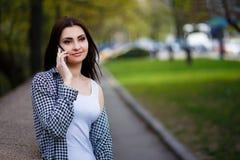 Mujer bastante elegante de los jóvenes que habla en el teléfono elegante en el parque Imagen de archivo libre de regalías