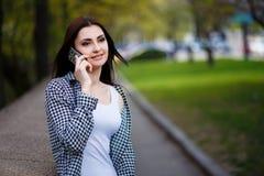 Mujer bastante elegante de los jóvenes que habla en el teléfono elegante en el parque Foto de archivo libre de regalías