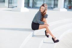 Mujer bastante elegante de los jóvenes que se sienta en las escaleras Imagenes de archivo