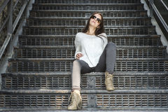Mujer bastante elegante de los jóvenes que se sienta en las escaleras Imagen de archivo libre de regalías