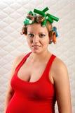 Mujer bastante embarazada con los rodillos del pelo Imagen de archivo libre de regalías