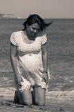 Mujer bastante embarazada que se arrodilla abajo en la playa Fotografía de archivo