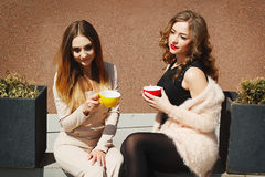Mujer bastante feliz de dos jóvenes que se sienta al aire libre y coffe de consumición Imágenes de archivo libres de regalías