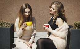 Mujer bastante feliz de dos jóvenes que se sienta al aire libre y coffe de consumición Imagen de archivo