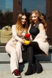 Mujer bastante feliz de dos jóvenes que se sienta al aire libre y coffe de consumición Fotografía de archivo libre de regalías
