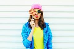 Mujer bastante fresca de la moda del retrato con la piruleta en ropa colorida sobre el fondo blanco gafas de sol rosadas de un am Fotos de archivo