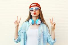Mujer bastante fresca en las gafas de sol y el casquillo rojo que se divierten sobre blanco Imágenes de archivo libres de regalías