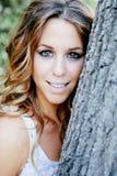 Mujer bastante fresca que se inclina en un tronco de árbol Fotos de archivo