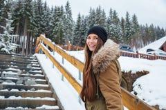 Mujer bastante joven alegre con el pelo largo que se coloca en las escaleras Imagen de archivo