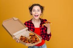 Mujer bastante joven alegre en camisa de tela escocesa que goza de la pizza Foto de archivo libre de regalías