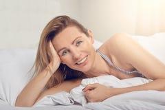 Mujer bastante joven amistosa feliz que se relaja en cama Imagenes de archivo