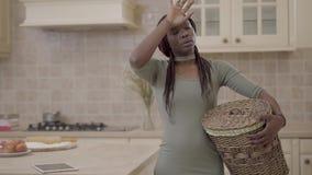 Mujer bastante joven cansada de la mujer afroamericana con la situación sucia de la cesta de lavadero en la cocina y pensar en ca metrajes