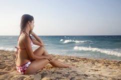 Mujer bastante joven con el bikiní que mira el océano Fotografía de archivo