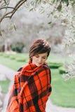 Mujer bastante joven con el corte de pelo corto que se coloca en un parque envuelto en una manta caliente Fotografía de archivo