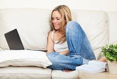 Mujer bastante joven con el ordenador portátil Imagenes de archivo