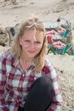Mujer bastante joven con el pelo rubio que se sienta afuera en la playa Imagen de archivo