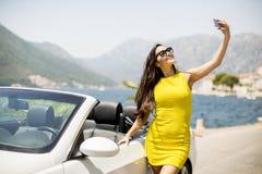 Mujer bastante joven con el teléfono móvil en coche blanco del cabriolé Fotos de archivo