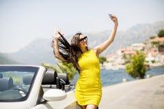 Mujer bastante joven con el teléfono móvil en coche blanco del cabriolé Foto de archivo