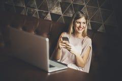 Mujer bastante joven con el teléfono móvil y el ordenador portátil en café Fotos de archivo