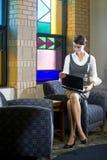 Mujer bastante joven con la computadora portátil en sala de espera Imagenes de archivo