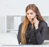 Mujer bastante joven con las auriculares que miran la pantalla del ordenador portátil Foto de archivo libre de regalías