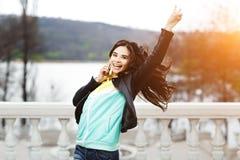 Mujer bastante joven con sonrisa hermosa que habla en el teléfono móvil en el parque en la puesta del sol Muchacha feliz Fotografía de archivo