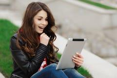 Mujer bastante joven con sonrisa hermosa usando la tableta en el parque Imagen de archivo