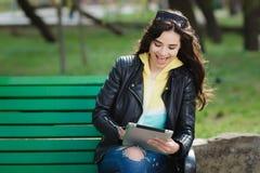 Mujer bastante joven con sonrisa hermosa usando la tableta en el parque en la puesta del sol Fotografía de archivo libre de regalías