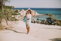 Mujer bastante joven con un bolso usando el tel?fono m?vil en la playa fotografía de archivo libre de regalías