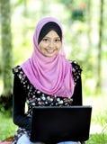 Mujer bastante joven con una computadora portátil Fotos de archivo