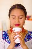 Mujer bastante joven del Headshot que lleva la blusa andina tradicional, café de consumición de la taza blanca Imagen de archivo libre de regalías