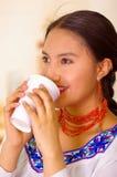 Mujer bastante joven del Headshot que lleva la blusa andina tradicional, café de consumición de la taza blanca Fotografía de archivo libre de regalías