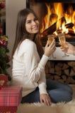 Mujer bastante joven delante de la chimenea Fotos de archivo