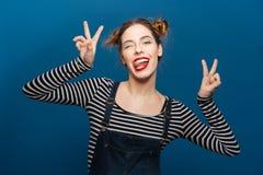 Mujer bastante joven divertida que muestra la lengua Imagen de archivo libre de regalías