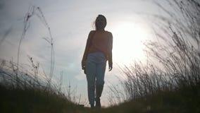 Mujer bastante joven en caminar al aire libre en la puesta del sol almacen de metraje de vídeo