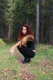 Mujer bastante joven en corsé con la piel en bosque del otoño Fotografía de archivo