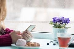 Mujer bastante joven en el café que bebe y que usa el teléfono móvil adentro el domingo por la mañana Imagenes de archivo