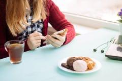 Mujer bastante joven en el café que bebe y que usa el teléfono móvil adentro el domingo por la mañana Imagen de archivo libre de regalías