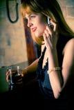 Mujer bastante joven en el contador de la barra, en el teléfono móvil Imagenes de archivo