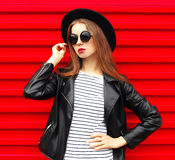 Mujer bastante joven en el estilo de la roca del negro de la moda que presenta sobre rojo colorido Fotografía de archivo